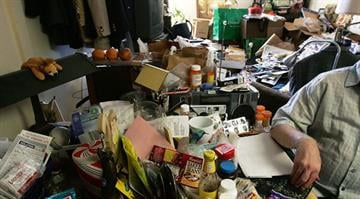 A man's kitchen table is loaded with things he has hoarded. Behind him is his living room. By Brendan Marks