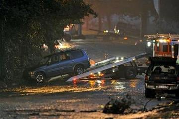 Workers clear vehicles from the scene of flash flood, caused by heavy rains, along Washington Blvd. where three people died while trapped in their car Friday, Aug. 19, 2011 in Pittsburgh. (AP Photo/Don Wright) By DON WRIGHT