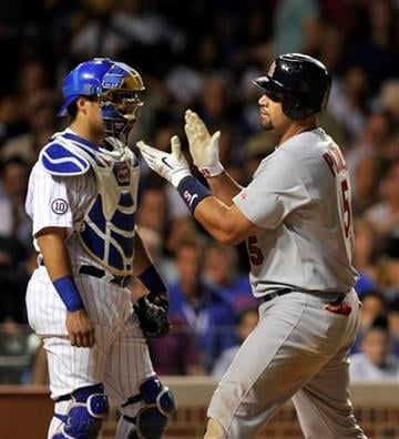 Chicago Cubs'  catcher Geovany Soto, left, looks on as the St. Louis Cardinals' Albert Pujols celebrates his solo home run during the fifth inning of a baseball game Sunday, Aug. 21, 2011, in Chicago. (AP Photo/Jim Prisching) By Jim Prisching