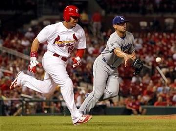 Los Angeles Dodgers relief pitcher Blake Hawksworth, right, tosses to first to throw out St. Louis Cardinals' Jon Jay during the seventh inning of a baseball game Tuesday, Aug. 23, 2011, in St. Louis. (AP Photo/Jeff Roberson) By Jeff Roberson