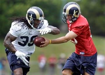 St. Louis Rams quarterback Sam Bradford, right, hands off the ball to running back Steven Jackson during NFL football training camp Saturday, July 30, 2011, in St. Louis. (AP Photo/Jeff Roberson) By Jeff Roberson
