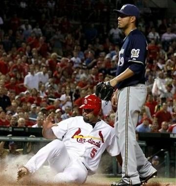St. Louis Cardinals' Albert Pujols, left, scores on a wild pitch by Milwaukee Brewers starting pitcher Yovani Gallardo, right, during the fifth inning of a baseball game Thursday, Aug. 11, 2011, in St. Louis. (AP Photo/Jeff Roberson) By Jeff Roberson