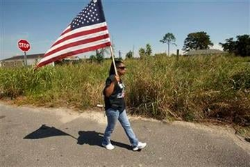 Phyllis Montana LeBlanc walks with an American flag through the Lower 9th Ward section of New Orleans during event commemorating the sixth anniversary of Hurricane Katrina, Monday, Aug. 29, 2011. (AP Photo/Gerald Herbert) By Gerald Herbert