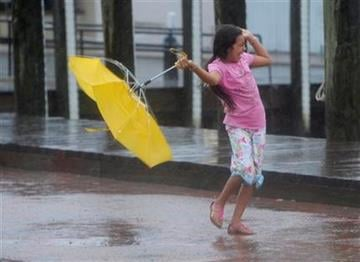 Kayla Mejia of Annapolis, Md. laughs as her umbrella turns inside out from the winds from Hurricane Irene as she visits City Dock in Annapolis, Md. on Saturday, Aug. 27, 2011. (AP Photo/Susan Walsh) By Susan Walsh