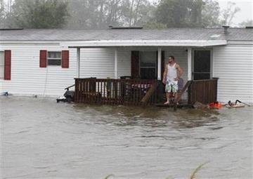 Jarod Wilton looks at the flood waters rising to his doorstep, Saturday, Aug. 27, 2011, in Alliance, N.C., as Hurricane Irene hits the North Carolina coast. (AP Photo/Chuck Burton) By Chuck Burton