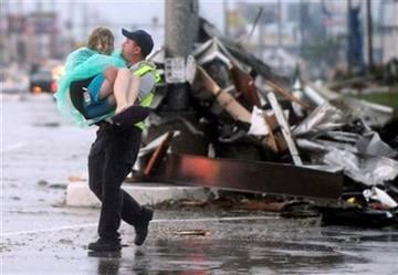 An emergency worker carries a girl to safety from the remains of Academy Sports  in Joplin, Mo. after a tornado struck the city on Sunday evening, May 22, 2011. (AP Photo/The Joplin Globe, Roger Nomer) By Roger Nomer