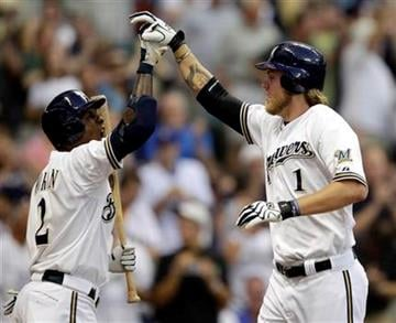Milwaukee Brewers' Corey Hart (1) is congratulated by Nyjer Morgan (2) after Hart hit a home run during the first inning of a baseball game against the St. Louis Cardinals, Wednesday, Aug. 31, 2011, in Milwaukee. (AP Photo/Morry Gash) By Morry Gash