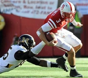 Missouri defensive end Aldon Smith, left, trips up Nebraska quarterback Taylor Martinez (3) in the first half of an NCAA college football game in Lincoln, Neb., Saturday, Oct. 30, 2010. (AP Photo/Dave Weaver) By Dave Weaver