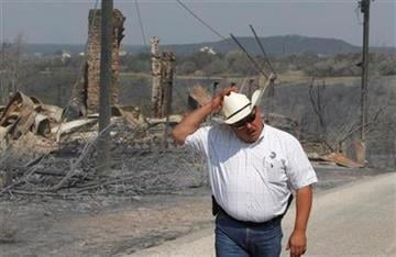 Palo Pinto County Sheriff Ira Mercer holds onto his cowboy hat as the wind picks up during a tour of an area destroyed by a wildfire at Possum Kingdom Lake, Texas, Wednesday, Aug. 31, 2011. (AP Photo/LM Otero) By LM Otero