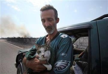 Mike Hester holds a cat he rescued from an area destroyed by a wildfire at Possum Kingdom Lake, Texas, Wednesday, Aug. 31, 2011, the day the fire swept through the neighborhood and destroyed 25 homes. (AP Photo/LM Otero) By LM Otero