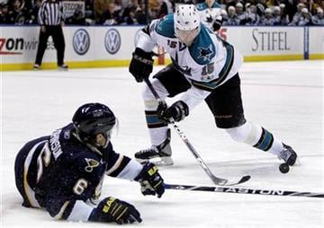 San Jose Sharks' Dany Heatley tries to control a loose puck as St. Louis Blues' Erik Johnson, left, defends during the third period of an NHL hockey game Saturday, Dec. 18, 2010, in St. Louis. The Sharks won 4-1. (AP Photo/Jeff Roberson) By Jeff Roberson