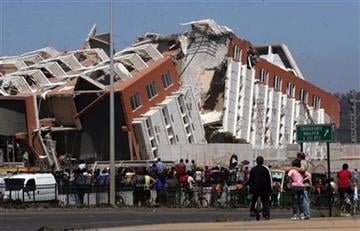 Residents look at a collapsed  building in Concepcion, Chile, Saturday Feb. 27, 2010 after an 8.8-magnitude struck central Chile. The epicenter was 70 miles (115 kilometers) from Concepcion,  Chile's second-largest city.(AP Photo) By STR
