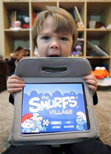 "In this photo taken Dec. 7, 2010, Sawyer Rummelhart, 4, holds his mothers iPad showing the game ""The Smurf's Village, "" at his families home in Gridley, Calif.(AP Photo/Rich Pedroncelli) By Rich Pedroncelli"