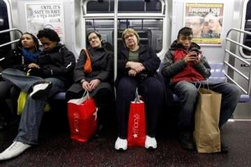In this Dec. 18, 2010 photo, shoppers ride the F-train, in New York. (AP Photo/Mary Altaffer) By Mary Altaffer