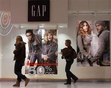 In this photo taken Dec. 6, 2010, people pass by advertising at a shopping mall in Springfield, Ill. (AP Photo/Seth Perlman) By Seth Perlman
