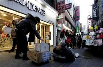 A handicapped man begs along a shopping street in Seoul, South Korea, Friday, Dec. 24, 2010. (AP Photo/Ng Han Guan) By Ng Han Guan