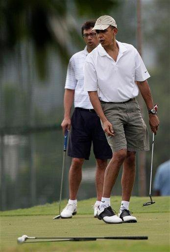President Barack Obama, right, and friend Mike Ramos, left, react to Obama's putt as they golf at Mid-Pacific County Club in Kailua, Hawaii, Tuesday, Dec. 28, 2010. (AP Photo/Carolyn Kaster) By Carolyn Kaster