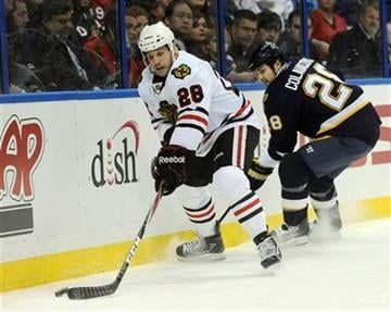 Chicago Blackhawks' Jake Dowell (28) gets past  St. Louis Blues' Carlo Colaiacovo, right, in the first period of an NHL hockey game Tuesday, Dec. 28, 2010, in St. Louis. (AP Photo/Bill Boyce) By Bill Boyce