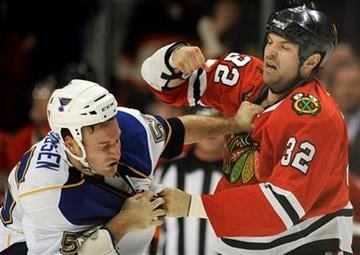 Chicago Blackhawks' John Scott right, fights with St. Louis Blues' Cam Janssen in the first period of a NHL hockey game in Chicago, Tuesday, Nov. 30, 2010. (AP Photo/Paul Beaty) By Paul Beaty