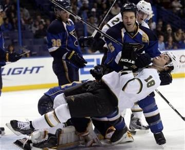 St. Louis Blues' Barret Jackman (5) takes down Dallas Stars' James Neal (18), who ran into Blues goaltender Jaroslav Halak, bottom, in the first period of an NHL hockey game, Sunday, Jan. 2, 2011, in St. Louis.(AP Photo/Tom Gannam) By Tom Gannam