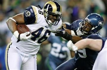 St. Louis Rams' Daniel Fells straight arms Seattle Seahawks' Aaron Curry, right, as he runs the ball  in the first half of an NFL football game, Sunday, Jan. 2, 2011, in Seattle. (AP Photo/John Froschauer) By John Froschauer