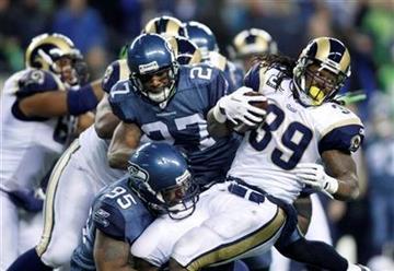 St. Louis Rams' Steven Jackson, right, is hit by Seattle Seahawks' Kentwan Balmer (95) with an assist from Jordan Babineaux (27) in the first half of an NFL football game, Sunday, Jan. 2, 2011, in Seattle. (AP Photo/John Froschauer) By John Froschauer