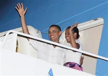 President Barack Obama and first lady  Michelle Obama, wave as they board Force One at Hickam Air Force Base in Honolulu, Monday, Jan. 3, 2011, en route to Washington after a family vacation. (AP Photo/Carolyn Kaster) By Carolyn Kaster