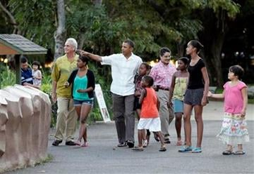 President Barack Obama walks with his daughters Sasha Obama, sixth from right, Malia Obama, second from right, and other family and friends through Honolulu Zoo in Honolulu, Monday, Jan. 3, 2011. (AP Photo/Carolyn Kaster) By Carolyn Kaster