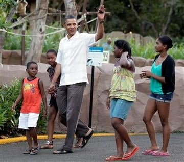 President Barack Obama waves as he walks with Xavier Nesbitt , right, his daughter Sasha Obama, second from right, and other family friends through Honolulu Zoo in Honolulu, Monday, Jan. 3, 2011. (AP Photo/Carolyn Kaster) By Carolyn Kaster