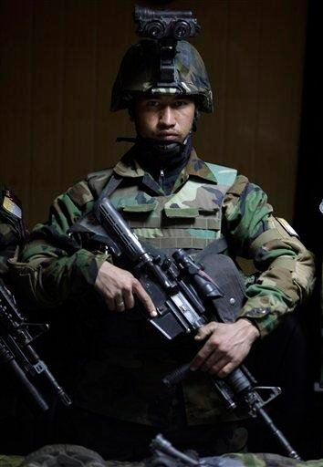 An Afghan Army commando stands in front of weapons on display for the media,  in Kabul, Afghanistan, Wednesday, Jan. 5, 2011. (AP Photo/Altaf Qadri) By Altaf Qadri