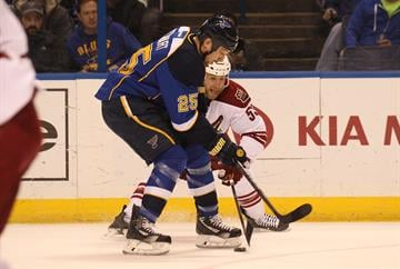 St. Louis Blues Chris Stewart tries to get his stick on the puck as he battles Phoenix Coyotes Derek Morris in the first period at the Scottrade Center in St. Louis on January 14, 2014.   UPI/Bill Greenblatt By BILL GREENBLATT
