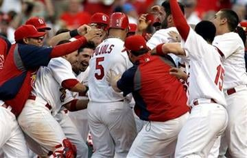 St. Louis Cardinals' Albert Pujols (5) is mobbed by teammates after hitting a walkoff home run to defeat the Chicago Cubs 5-4 during the 12th inning of a baseball game on Saturday, June 4, 2011, in St. Louis. (AP Photo/Jeff Roberson) By Jeff Roberson
