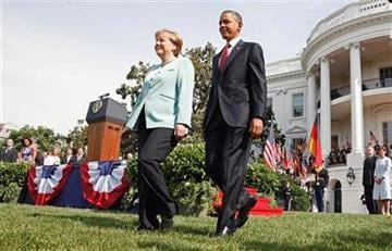 President Barack Obama and German Chancellor Angela Merkel walk across the South Lawn of the White House in Washington, Tuesday, June 7, 2011, during an arrival ceremony.  (AP Photo/Carolyn Kaster) By Carolyn Kaster