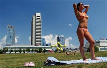 A sunbathers basks in the hot sun at the downtown in Vilnius, Lithuania, Thursday, June 09, 2011. Hot weather has set in with temperatures rising up to 29 Celsius (84 Fahrenheit ) in Vilnius (AP Photo/Mindaugas Kulbis) By Mindaugas Kulbis