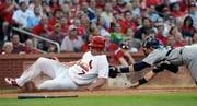 St. Louis Cardinals' Matt Holliday (7) scores past the tag of Seattle Mariners' Rob Johnson on a fly ball by Ryan Ludwick in the third inning of a baseball game Monday, June 14, 2010, in St. Louis. (AP Photo/Bill Boyce) By Bill Boyce