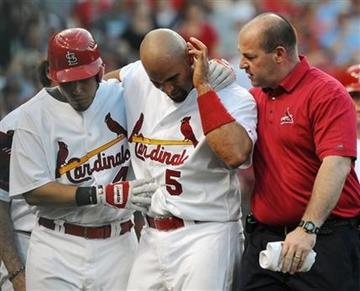 El dominicano Albert Pujols de los Cardenales de San Luis (5) se revisa la oreja luego de recibir un pelotazo. Lo ayudan Yadier Molina (4) y Greg Hauck, a la derecha, el lunes 14 de junio del 2010, en San Luis. (Foto AP/Bill Boyce) By Bill Boyce