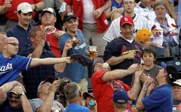 Fans try to catch a foul ball hit by St. Louis Cardinals' Jason LaRue during the second inning of a baseball game against the Kansas City Royals, Friday, June 25, 2010, in Kansas City, Mo. (AP Photo/Charlie Riedel) By Charlie Riedel