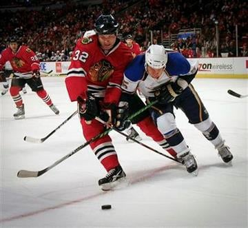 St. Louis Blues' Cam Janssen gets his stick tied up by Chicago Blackhawks' John Scott during the first period of a preseason NHL hockey game Sunday, Oct. 3, 2010, in Chicago. (AP Photo/Charles Cherney) By Charles Cherney