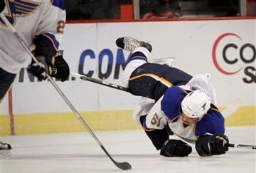 St. Louis Blues' David Spina gets pulled down by the stick of the Chicago Blackhawks' Tomas Kopecky during the first period of a preseason NHL hockey game Sunday, Oct. 3, 2010, in Chicago. (AP Photo/Charles Cherney) By Charles Cherney