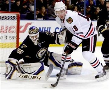 Chicago Blackhawks' Jonathan Toews (19) tries to control the puck as St. Louis Blues goalie Chris Mason defends during the first period of an NHL hockey game Saturday, Feb. 6, 2010, in St. Louis. (AP Photo/Jeff Roberson) By Jeff Roberson