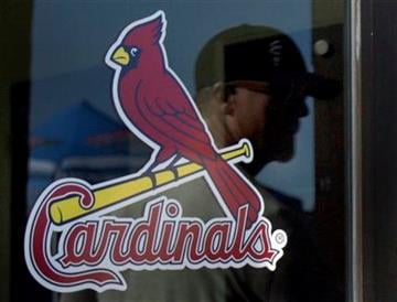 The reflection of St. Louis Cardinals hitting coach Mark McGwire is seen on a door as he enters the Cardinals' offices to report for spring training baseball Wednesday, Feb. 17, 2010, in Jupiter, Fla. (AP Photo/Jeff Roberson) By Jeff Roberson
