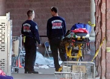 Emergency personnel stand at the scene of a shooting that authorities claim involved Rep. Gabrielle Giffords, D-Ariz., in Tucson, Ariz., on Saturday, Jan. 8, 2011. (AP Photo/Arizona Daily Star, Dean Knuth) NO MAGS, NO SALES, MANDATORY CREDIT By Dean Knuth
