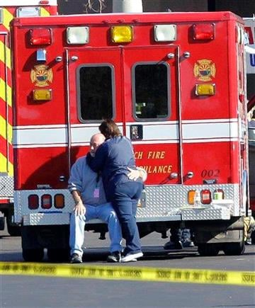 Two people embrace each other at the scene where Rep. Gabrielle Giffords, D-Ariz., and others were shot outside a Safeway grocery store in Tucson, Ariz. on Saturday, Jan. 8, 2011. (AP Photo/Matt York) By Matt York