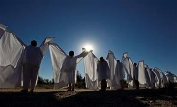 People dressed as angels stand outside the St. Elizabeth Ann Seton Church before the funeral of U.S. District Judge John Roll on Friday, Jan. 14, 2011, in Tucson, Ariz. (AP Photo/Chris Carlson) By Chris Carlson