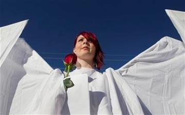 Jessica Dewitt, of Phoenix, is dressed as an angel outside the St. Elizabeth Ann Seton Church for the funeral of U.S. District Judge John Roll on Friday, Jan. 14, 2011, in Tucson, Ariz. (AP Photo/Chris Carlson) By Chris Carlson