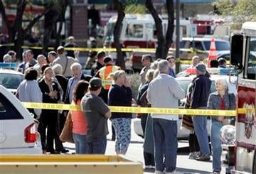 People gather at the scene of a shooting involving Rep. Gabrielle Giffords, D-Ariz., on Jan. 8, 2011 in Tucson, Ariz.  (AP Photo/Arizona Daily Star, Dean Knuth)  NO MAGS, NO SALES, MANDATORY CREDIT By Dean Knuth/Arizona Daily Star