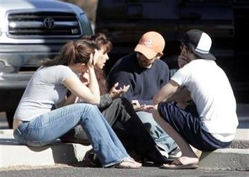 People talk at the scene of a shooting involving Rep. Gabrielle Giffords, D-Ariz., on Jan. 8, 2011 in Tucson, Ariz.  (AP Photo/Arizona Daily Star, Dean Knuth)  NO MAGS, NO SALES, MANDATORY CREDIT By Dean Knuth/Arizona Daily Star