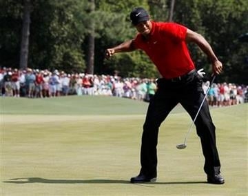 Tiger Woods reacts after an eagle putt on the eighth hole during the final round of the Masters golf tournament Sunday, April 10, 2011, in Augusta, Ga. (AP Photo/David J. Phillip) By David J. Phillip
