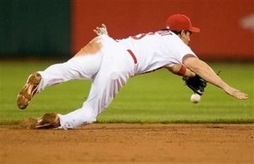 St. Louis Cardinals shortstop Ryan Theriot dives but misses a ball hit by Cincinnati Reds' Miguel Cairo during the second inning of a baseball game Friday, April 22, 2011, in St. Louis. (AP Photo/Jeff Curry) By Jeff Curry