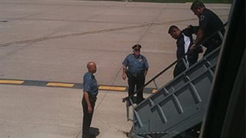 Photo of suspect who attempted to open a flight door in mid-air.  He is being led off the plane by Lambert-St. Louis Airport officials.  Credit: Paige Hoppie By Paige Hoppie